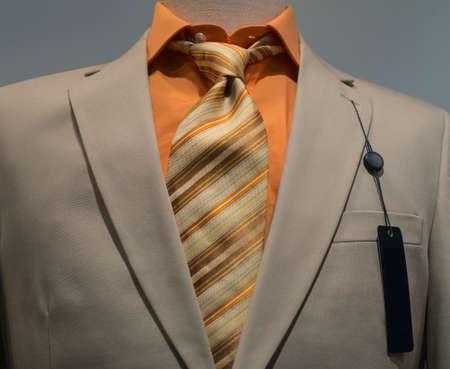 오렌지 셔츠, 스트라이프 넥타이와 왼쪽 된 옷깃에 빈 검은 태그 베이지 색 재킷의 근접
