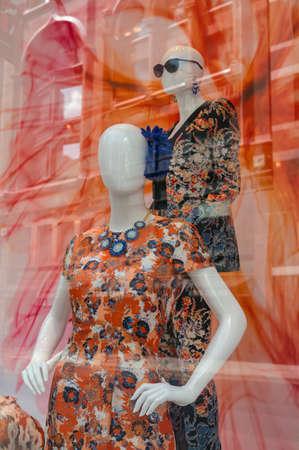 상점 창에 밝은 화려한 드레스와 두 개의 다채로운 마네킹 유리에 반영하는 거리의 풍경
