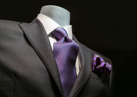 menswear: Close-up of a dark gray jacket with striped purple tie and handkerchief on black background