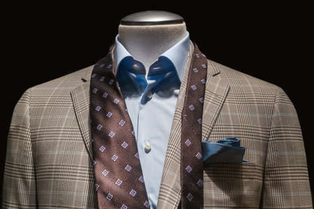 untied: Close-up of a tan checkered jacket with blue shirt, untied brown tie and teal handkerchief on black background   Stock Photo