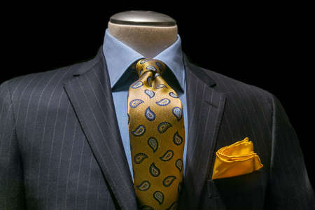 menswear: Close-up of a gray striped jacket with blue shirt, patterned golden yellow tie and handkerchief on black background