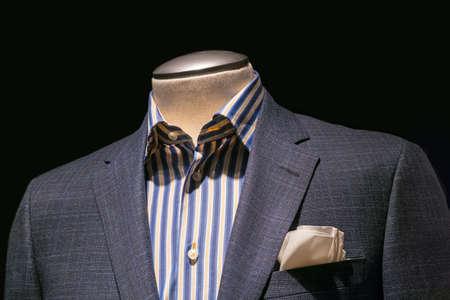 검정색 배경에 파란색 노란색 스트라이프 셔츠와 크림 손수건과 함께 회색 바둑판 무늬 자켓의 근접