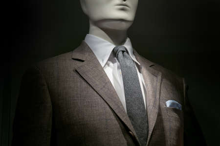 menswear: Close-up of a mannequin in a brown checkered jacket with white shirt, grey tie and striped blue   white handkerchief on black background