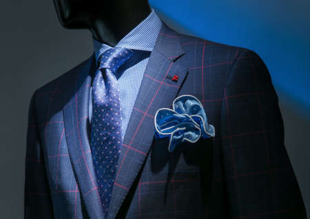male mannequin: Close-up of a blue   red checkered jacket with checkered blue shirt, patterned blue tie and handkerchief on dark background
