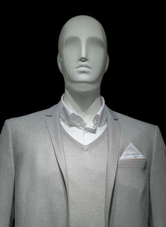 Mannequin in a light gray jacket, sweater and white shirt on black background  Clipping path included  photo