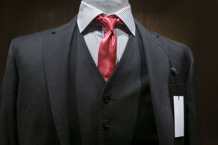Close-up of a dark gray striped suit with striped white shirt, red tie and a blank white tag on the left lapel   photo