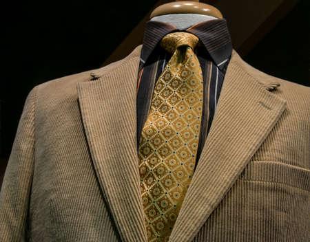 어두운 배경에 검은 오렌지 스트라이프 셔츠와 베이지 색 코듀로이 재킷의 근접 패턴 노란색 넥타이