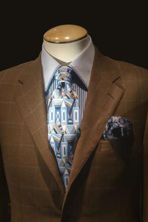 줄무늬 셔츠와 어두운 배경에 파란색 무늬 넥타이와 갈색 체크 무늬 자 켓에 마네킹