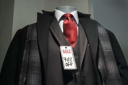 """검은 코트, 3 피스 정장, 스카프, 빨간 넥타이와 """"세일 70 % OFF""""태그 마네킹."""
