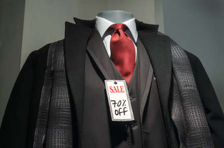 Mannequin with black coat, 3-piece suit, scarf, red tie and Sale 70% off tag. photo