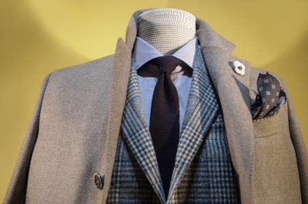 베이지 색 코트, 체크 무늬 자 켓, 스트라이프 셔츠와 어두운 파란색 넥타이에 마네킹의 닫습니다. 스톡 콘텐츠