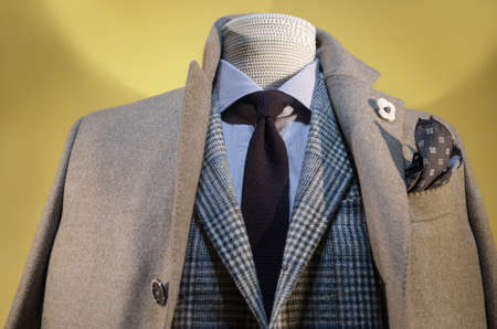 Close up of a mannequin in beige coat, checkered Jacket, striped shirt and dark blue tie. photo