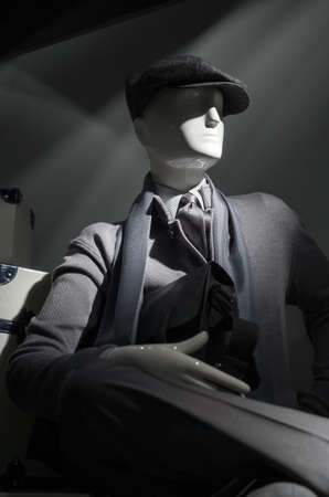 menswear: Mannequin in gray sweater, cap, striped shirt, scarf and tie.