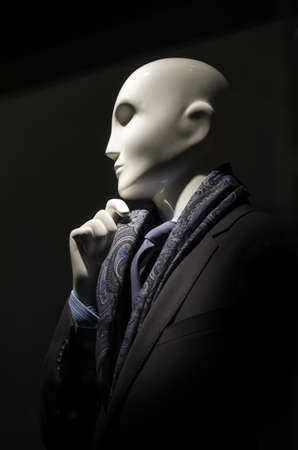 Mannequin in black suit with checkered shirt, purple tie and scarf.