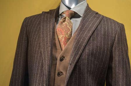 닫기 갈색 줄무늬 재킷, 갈색 조끼, 체크 무늬 셔츠와 브라운 & 오렌지 넥타이 마네킹을 닫습니다.