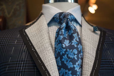Close-up of an unfinished checkered jacket with white thread stitches and blue patterned tie