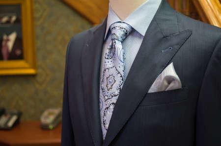 흰색 스레드 바늘 푸른 무늬 넥타이와 미완성 된 체크 무늬 재킷의 근접