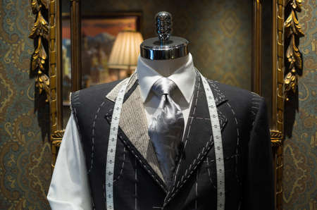 tailor suit: Unfinished gray jacket with white thread stitches and white measuring tape  Mirror on the background
