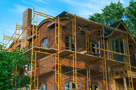 Luxury brick mansion under construction with scaffolding ariund it  photo