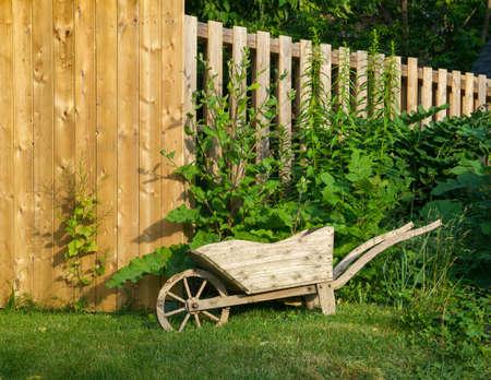 Decorative wooden wheelbarrow planter near wooden fence  photo