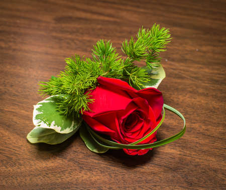 buttonhole: Beautiful boutonniere with rose on a table  Stock Photo