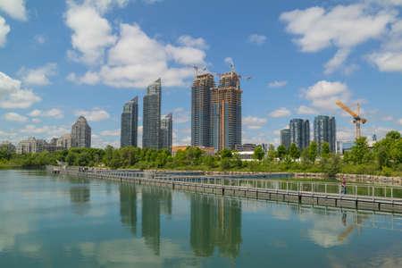 새로운 고층 건물, 일부는 여전히 하늘과 구름을 반영하는 연못 근처에 건설 중이다.