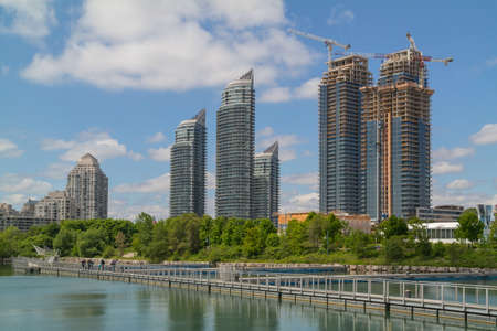 새로운 고층 건물, 일부는 여전히 하늘과 구름을 반영하는 연못 근처에서 건설 중이다.