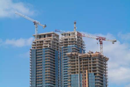 Nieuwe high-rise gebouwen in aanbouw met kranen Sky en wolken op de achtergrond Stockfoto