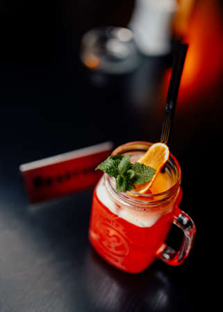 Delicious exotic red cocktail served with dried lemon and mint