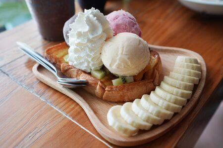 ice cream banana on woon board. On wood table. Imagens - 132526521