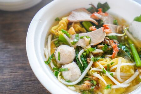 Yellow egg noodle with red roast pork dumpling and chinese cabbage vegetable in soup bowl on wooden table top view Imagens - 132824982