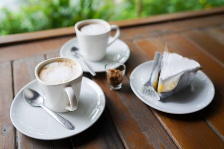 Coffee cup and cake on wooden table background