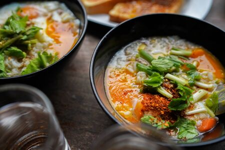 Thai congee with minced pork and egg is a favorite breakfast for Thai people. on wood table texture.