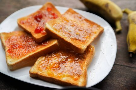 Plate with slices of bread and delicious strawberry jam on wooden table Imagens