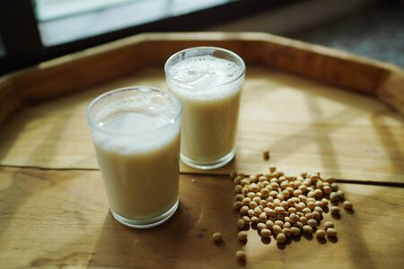 Soy milk homemade in glass cup decorated by soybean on wooden table background.