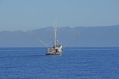 Commercial fishing boat trolling California coastline Stok Fotoğraf