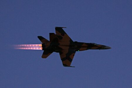 f18: F-18 Hornet flying at twilight air show Editorial