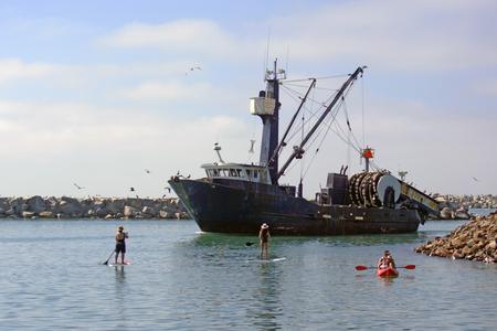 commercial fishing net: Fishing boat returning to harbor Stock Photo