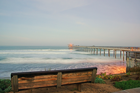 oceanography: Beach cliff bench at San Diego pier during foggy sunrise