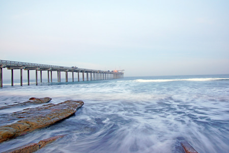 oceanography: Beach pier with surf movement during winter foggy sunrise Stock Photo