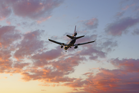 airplane landing: Jet airplane landing into the sunset at Los Angeles, California Stock Photo