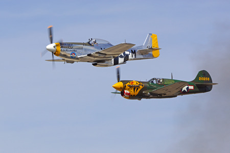 Airplane P-51 and P-40 flying together at air show