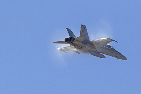 Airplane F-18 Hornet jet fighter breaking the sound barrier