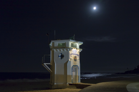 Beach lifeguard tower with full moon at night Stock Photo