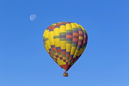 Hot air balloon flying with the moon