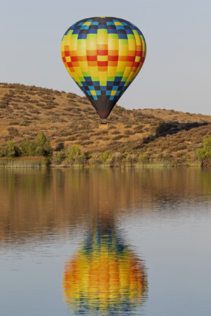 Hot air balloon flying above California lake Stock Photo