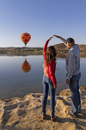 Balloon launch at California lake with couple viewing Stock Photo