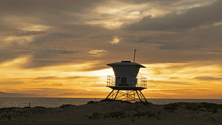 Sunset at a California beach life guard station silhouette Stock fotó