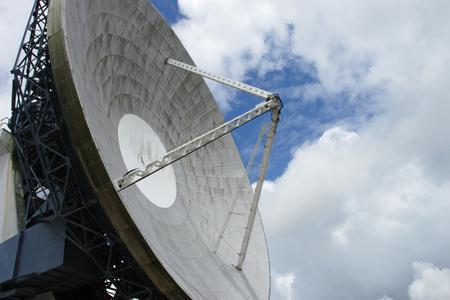 satelite: satelite dish agianst blue patch in cloudy sky