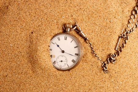 bezel: Antique pocket watch on sand